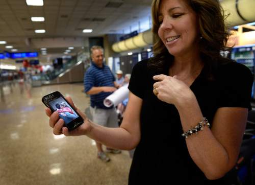 Scott Sommerdorf   |  The Salt Lake Tribune While waiting for her son Tyler to return home from his mission in Peru, Sheri Randolph shows a photo of her hugging her son as he left on the mission two years prior. At the Salt Lake International Airport, Wednesday, September 9, 2015.
