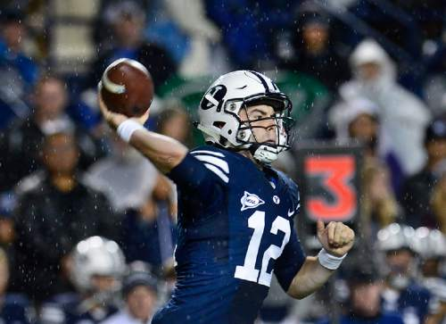 Scott Sommerdorf   |  The Salt Lake Tribune BYU quarterback Tanner Mangum (12) throws as rain comes down during second half play. BYU beat UCONN 30-13, Friday, October 2, 2015.
