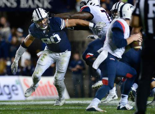 Scott Sommerdorf   |  The Salt Lake Tribune BYU defensive lineman Bronson Kaufusi (90) spins as he rushes Connecticut quarterback Bryant Shirreffs (4) during second half play. BYU beat UCONN 30-13, Friday, October 2, 2015.
