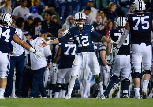 Scott Sommerdorf   |  The Salt Lake Tribune BYU quarterback Tanner Mangum (12) congratulates the field goal team after they were successful on an attempt to give BYU their final total of 30. BYU beat UCONN 30-13, Friday, October 2, 2015.