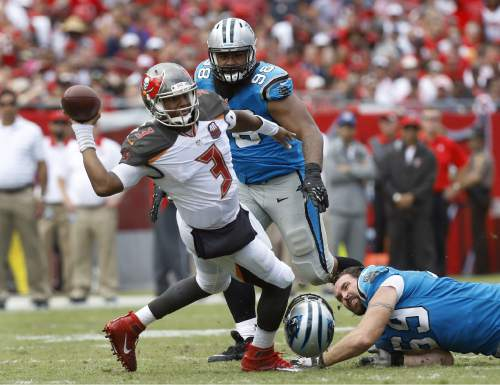 Tampa Bay Buccaneers quarterback Jameis Winston (3) loses his balance after getting tripped up by Carolina Panthers' Jared Allen (69) and Star Lotulelei (98) during the third quarter of an NFL football game Sunday, Oct. 4, 2015, in Tampa, Fla. (AP Photo/Brian Blanco)