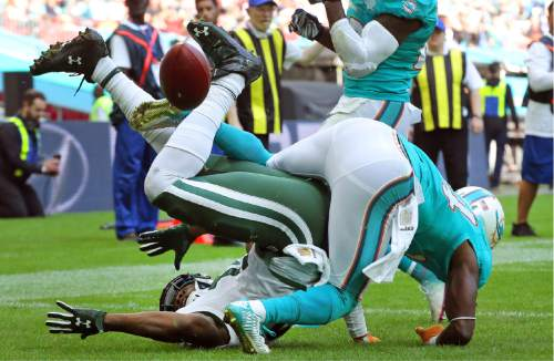 New York Jets' Brandon Marshall, left, becomes entangled with Miami Dolphins' Brice McCain as he fails to catch the ball in the end zone during an NFL football game at Wembley Stadium in London, Sunday, Oct. 4, 2015. (AP Photo/Tim Ireland)