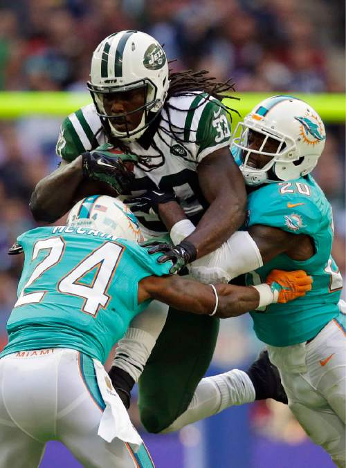 New York Jets' Chris Ivory, center, is tackled by Miami Dolphins' Brice McCain, left, and Reshad Jones during an NFL football game at Wembley Stadium in London, Sunday, Oct. 4, 2015. (AP Photo/Matt Dunham)