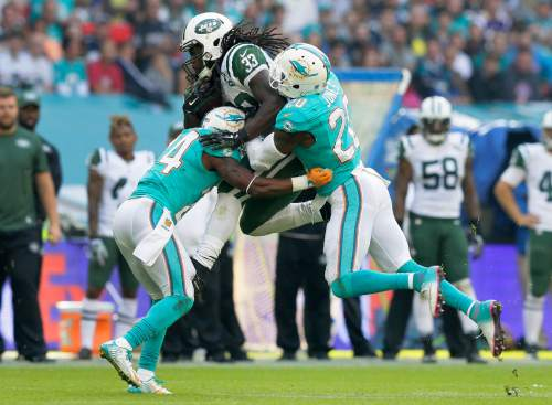New York Jets' Chris Ivory, centre, is tackled by Miami Dolphins' Brice McCain, left, and Reshad Jones during the NFL football game between the New York Jets and the Miami Dolphins and at Wembley stadium in London, Sunday, Oct. 4, 2015.  (AP Photo/Tim Ireland)