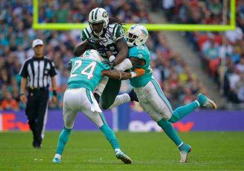 New York Jets' Chris Ivory, centre, is tackled by Miami Dolphins' Brice McCain, left, and Reshad Jones during the NFL football game between the New York Jets and the Miami Dolphins and at Wembley stadium in London, Sunday, Oct. 4, 2015. (AP Photo/Matt Dunham)