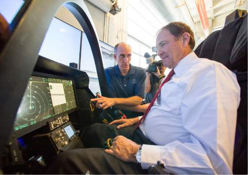 Rick Egan  |  The Salt Lake Tribune F-35 Cockpit Simulator Pilot Eric Best (left) gives some instructions to Gov. Gary Herbert, as he sits in the cockpit of the F-35 simulator.  Lockheed Martin and Hill Air Force Base teamed up to bring the F-35 interactive cockpit demonstrator to the University Of Utah Wednesday, October 7, 2015.