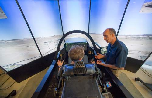 Rick Egan  |  The Salt Lake Tribune  F-35 Cockpit Simulator Pilot Eric Best (right) gives some instructions to University of Utah Engineering graduate student, Beau Freckleton, as he sits in the cockpit of the F-35 simulator.  Lockheed Martin and Hill Air Force Base teamed up to bring the F-35 interactive cockpit demonstrator to the University Of Utah Wednesday, October 7, 2015.