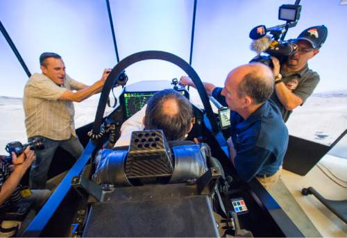 Rick Egan  |  The Salt Lake Tribune  F-35 Cockpit Simulator Pilot Eric Best (right) gives Gov. Gary Herbert some instructions to University of Utah Engineering graduate student, Beau Freckleton, as he sits in the cockpit of the F-35 simulator.  Lockheed Martin and Hill Air Force Base teamed up to bring the F-35 interactive cockpit demonstrator to the University Of Utah Wednesday, October 7, 2015.