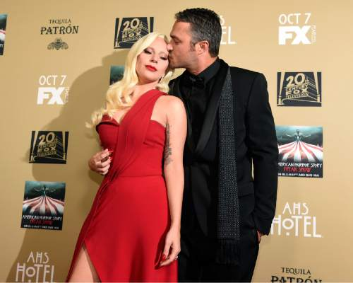 """Lady Gaga, left, and Taylor Kinney arrive at the Los Angeles premiere screening of """"American Horror Story: Hotel"""" at Regal Cinemas L.A. Live on Saturday, Oct. 3, 2015. (Photo by Chris Pizzello/Invision/AP)"""