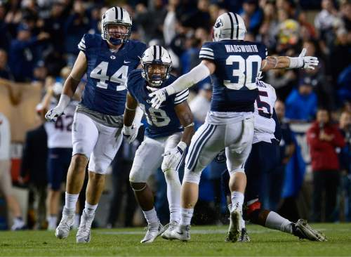 Scott Sommerdorf   |  The Salt Lake Tribune BYU defensive back Michael Shelton (18) comes up celebrating after intercepting a pass to help seal the BYU win during second half play. BYU beat UCONN 30-13, Friday, October 2, 2015. BYU team mate BYU Michael Wadsworth (30) and Remington Peck (44) help him celebrate.