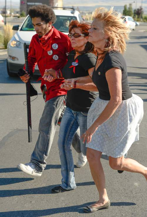 Francisco Kjolseth | The Salt Lake Tribune Susan Hunt, center, holds her son Kerahn, left, and her sister Cindy Moss, as they make the final run made by Susan's son Darrien Hunt before being shot and killed by police for carrying an ornamental sword in Saratoga Springs one year ago.