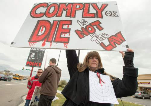 Rick Egan  |  The Salt Lake Tribune  Linda Spencer holds a sign, during a rally in Saratoga Springs, for Darrien Hunt, who was fatally shot by two Saratoga Springs, Friday, November 14, 2014