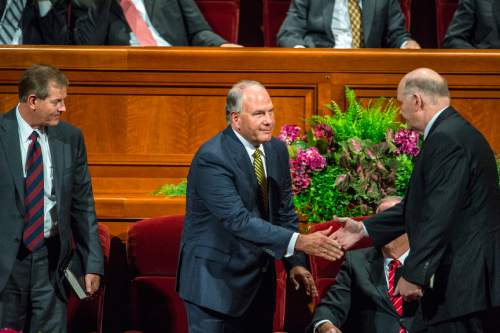 Chris Detrick  |  The Salt Lake Tribune New apostles Dale G. Renlund and Ronald A. Rasband shake hands during afternoon session of the 185th LDS General Conference at  the Conference Center in Salt Lake City Saturday October 3, 2015.  Gary E. Stevenson is at left.
