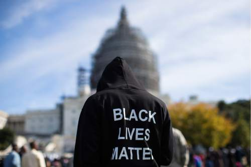 """Neal Blair, of Augusta, Ga., wears a hoodie which reads, """"Black Lives Matter"""" as stands on the lawn of the Capitol building during a rally to mark the 20th anniversary of the Million Man March, on Capitol Hill, on Saturday, Oct. 10, 2015, in Washington. Black men from around the nation returned to the capital calling for changes in policing and in black communities. (AP Photo/Evan Vucci)"""