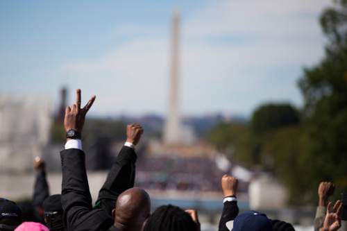 People put their hands in the air during a rally to mark the 20th anniversary of the Million Man March, on Capitol Hill, on Saturday, Oct. 10, 2015, in Washington. Waving flags, carrying signs and listening to speeches and songs, the crowd gathered at the U.S. Capitol and spread down the Mall under on a sunny and breezy fall day. (AP Photo/Evan Vucci)