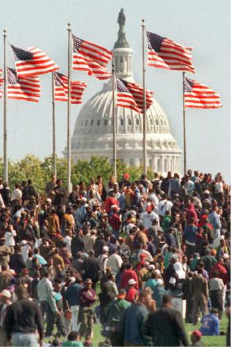FILE - In this Monday, Oct. 16, 1995 file photo, with the Capitol in the background, participants in the Million Man March gather on the Washington Monument grounds in Washington. (AP Photo/Charles Tasnadi)
