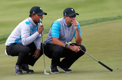 International team player Adam Scott, right, of Australia and his playing partner Anirban Lahiri of India line up a putt on the 10th hole during their four ball match at the Presidents Cup golf tournament at the Jack Nicklaus Golf Club Korea, in Incheon, South Korea, Saturday, Oct. 10, 2015.(AP Photo/Lee Jin-man)