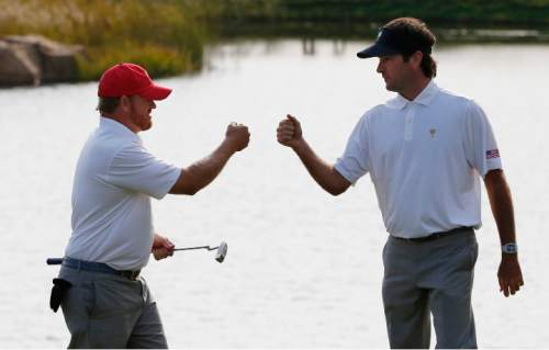 United States' J.B. Holmes, left, and teammate Bubba Watson celebrate on the ninth hole during their four ball match at the Presidents Cup golf tournament at the Jack Nicklaus Golf Club Korea, in Incheon, South Korea, Saturday, Oct. 10, 2015.(AP Photo/Lee Jin-man)