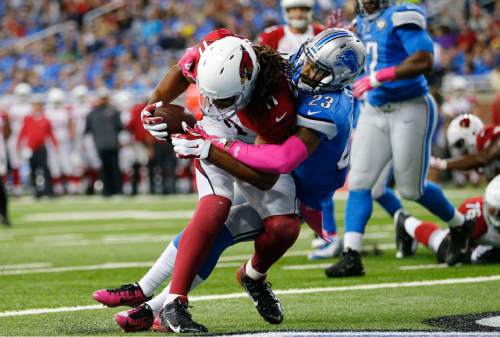 Arizona Cardinals wide receiver Larry Fitzgerald (11) is tackled by Detroit Lions cornerback Darius Slay (23) before falling into the end zone for a touchdown during the second half of an NFL football game, Sunday, Oct. 11, 2015, in Detroit. (AP Photo/Rick Osentoski)