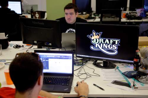 FILE- In this Sept. 9, 2015, file photo, Len Don Diego, marketing manager for content at DraftKings, a daily fantasy sports company, works at his station at the company's offices in Boston. The daily fantasy sports industry is eyeing a breakout season as NFL games begin. And its two dominant companies, DraftKings and FanDuel, are touting lucrative opening week prizes to try to draw more customers as more competitors pop up. (AP Photo/Stephan Savoia, File)