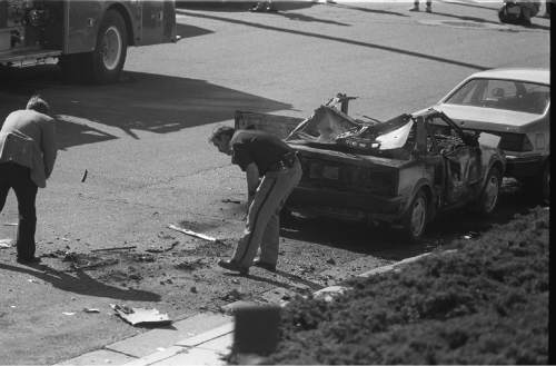 Tribune file photo Investigators examine what is left of Mark Hofmann's car after one of his bombs blew up, injuring him, in 1985.
