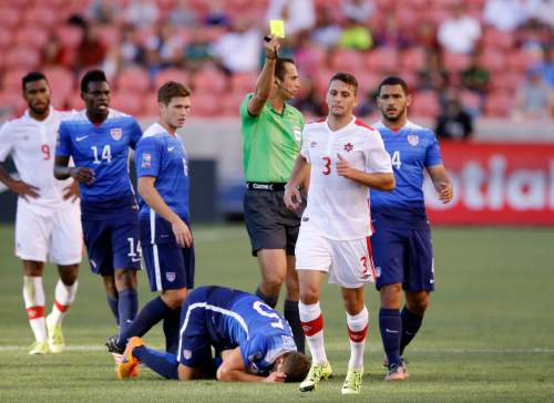 Canada midfielder Giuliano Frano (3) receives a yellow card after he tackled United States midfielder Marc Pelosi (15) in the first half of a CONCACAF Men's Olympic qualifying  soccer match Tuesday, Oct. 13, 2015, in Salt Lake City. (AP Photo/Rick Bowmer)