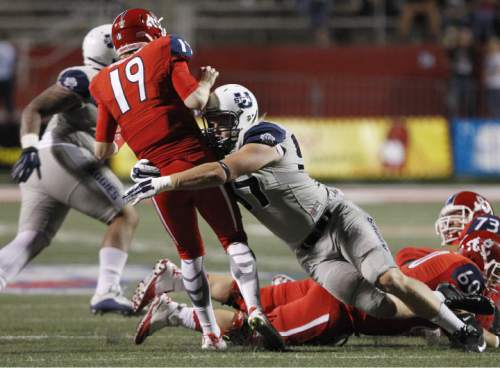 Utah State's Jordan Nielsen wraps up Fresno State's Kilton Anderson after Anderson released a pass during the second half of an NCAA college football game in Fresno, Calif., Saturday, Oct. 10, 2015. (AP Photo/Gary Kazanjian)