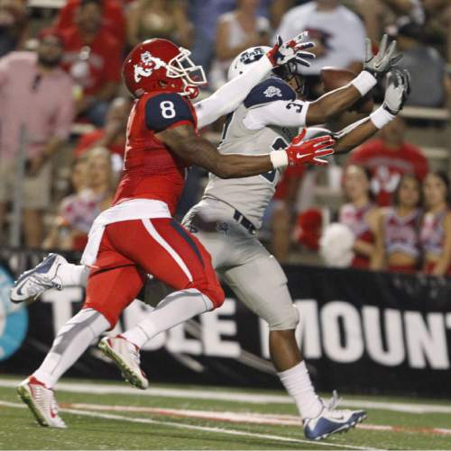 Utah State's Devin Centers catches an interception against Fresno State's Da'Mari Scott during the first half of an NCAA college football game in Fresno, Calif., Saturday, Oct. 10, 2015. (AP Photo/Gary Kazanjian)