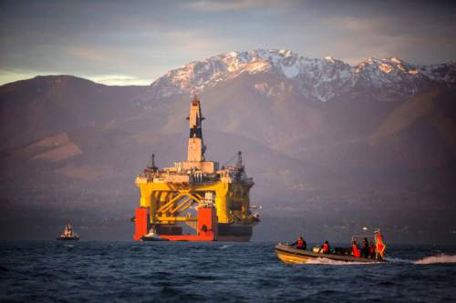 FILE - In this April 17, 2015 file photo, a small boat crosses in front of the Transocean Polar Pioneer, a semi-submersible drilling unit that Royal Dutch Shell leases from Transocean Ltd., as it arrives in Port Angeles, Wash. aboard a transport ship after traveling across the Pacific before its eventual Arctic destination. The Interior Department announced Friday, Oct. 16,  it is canceling future lease sales and will not extended current leases in Arctic waters off Alaska's northern coast, a decision that significantly reduces the chances for future Arctic offshore drilling.  (Daniella Beccaria/seattlepi.com via AP, File) MAGS OUT; NO SALES; SEATTLE TIMES OUT; TV OUT; MANDATORY CREDIT