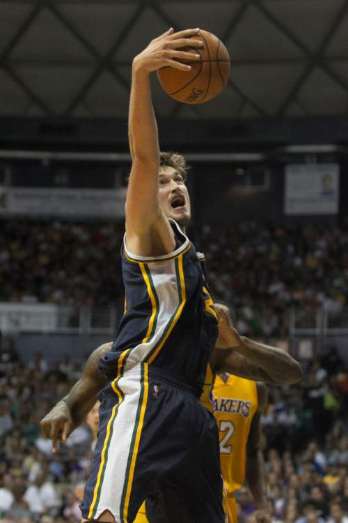 Utah Jazz center Tibor Pleiss (21) grabs a rebound over the Los Angles Lakers during the fourth quarter of a preseason NBA basketball game, Sunday, Oct. 4. 2015, in Honolulu.  The Jazz defeated the Lakers 91-71.  (AP Photo/Marco Garcia)
