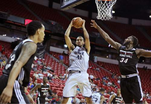 Utah Jazz's Trey Lyles, center, grabs a rebound past Miami Heat's Gabriel Olaseni (34) and Shabazz Napier during the second half of an NBA summer league basketball game Saturday, July 11, 2015, in Las Vegas. (AP Photo/Ronda Churchill)
