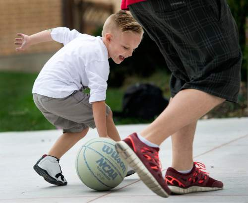 Steve Griffin  |  The Salt Lake Tribune  J.P. Gibson reverses his dribble as he plays with his father, Josh, on their home court in Layton, Utah Wednesday, September 30, 2015.   Gibson captured the hearts of many when the 5-year-old got the chance to participate in a Utah Jazz scrimmage last season. A year later, he is cancer free.