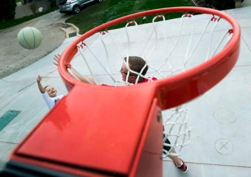 Steve Griffin  |  The Salt Lake Tribune  J.P. Gibson shoots a jumper over his father, Josh, on their home court in Layton, Utah Wednesday, September 30, 2015.   Gibson captured the hearts of many when the 5-year-old got the chance to participate in a Utah Jazz scrimmage last season. A year later, he is cancer free.