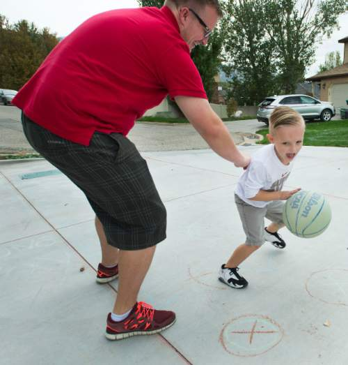 Steve Griffin  |  The Salt Lake Tribune  J.P. Gibson dribbles past his father, Josh, on their home court in Layton, Utah Wednesday, September 30, 2015.   Gibson captured the hearts of many when the 5-year-old got the chance to participate in a Utah Jazz scrimmage last season. A year later, he is cancer free.