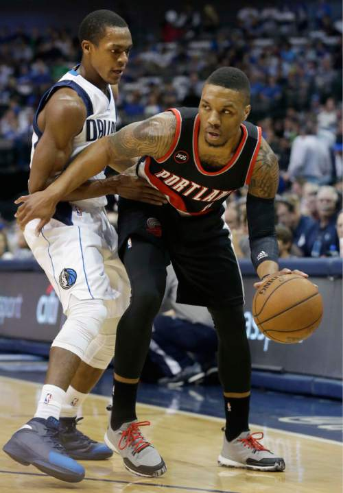 Portland Trail Blazers guard Damian Lillard, right, is defended by Dallas Mavericks guard Rajon Rondo during the first half of an NBA basketball game Wednesday, April 15, 2015, in Dallas. (AP Photo/LM Otero)
