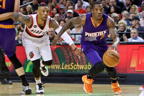 Phoenix Suns guard Eric Bledsoe, right, drives past Portland Trail Blazers guard Damian Lillard during the first half of an NBA basketball game in Portland, Ore., Monday, March 30, 2015.  (AP Photo/Craig Mitchelldyer)