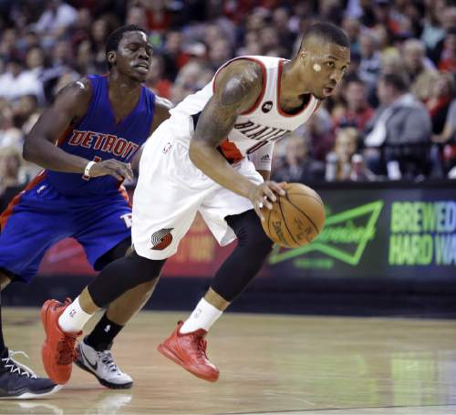 Portland Trail Blazers guard Damian Lillard, right, breaks to the basket past Detroit Pistons guard Reggie Jackson during the second half of an NBA basketball game in Portland, Ore., Friday, March 13, 2015. The Trail Blazers won 118-99. (AP Photo/Don Ryan)