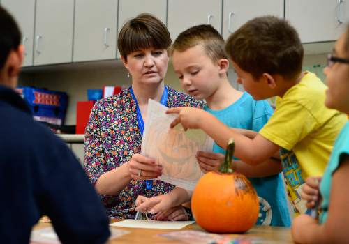 Scott Sommerdorf   |  The Salt Lake Tribune Plymouth Elementary teacher Tara Fredley checks the work of Boston Richardson, center, and Jonathan Hernandez who were decorating pumpkins with her 2nd grade class, Thursday, October 1, 2015. Fredley is one of the most experienced teachers at the school.