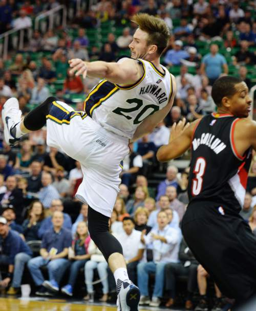 Steve Griffin  |  The Salt Lake Tribune  Utah Jazz guard Gordon Hayward (20) falls to the ground after being pulled down from behind by Portland Trail Blazers guard C.J. McCollum (3) late in the second half of the Utah Jazz versus the Portland Trailblazers preseason NBA basketball game at EnergySolutions Arena in Salt Lake City, Monday, October 12, 2015. McCollum was called for a flagrant foul and ejected from the game.