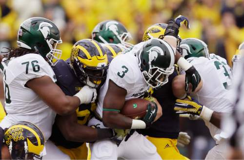 Michigan State running back LJ Scott (3) is stopped during the first half of an NCAA college football game against Michigan, Saturday, Oct. 17, 2015, in Ann Arbor, Mich. (AP Photo/Carlos Osorio)