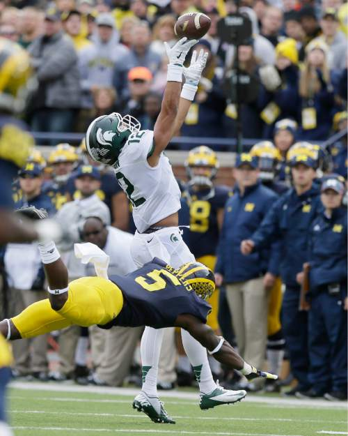 Michigan State wide receiver R.J. Shelton (12) is hit by Michigan safety Jabrill Peppers (5) during the first half of an NCAA college football game, Saturday, Oct. 17, 2015, in Ann Arbor, Mich. Peppers was called for pass interference on the play. (AP Photo/Carlos Osorio)