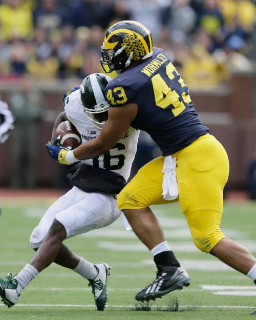 Michigan State wide receiver Aaron Burbridge (16) is tackled by Michigan defensive end Chris Wormley (43) during the first half of an NCAA college football game, Saturday, Oct. 17, 2015, in Ann Arbor, Mich. (AP Photo/Carlos Osorio)