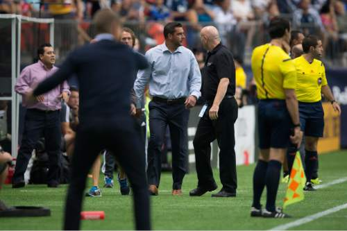 Real Salt Lake head coach Jeff Cassar, center, leaves the field after being ejected by referee Chris Penso during the first half of an MLS soccer game against the Vancouver Whitecaps in Vancouver, British Columbia, Saturday, Aug. 8, 2015. (Darryl Dyck/The Canadian Press via AP) MANDATORY CREDIT