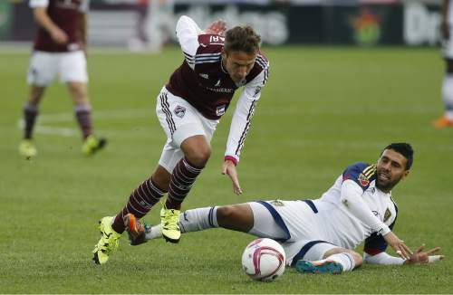 Colorado Rapids midfielder Lucas Pittinari, (22), left, tries to avoid getting tripped up by Real Salt Lake midfielder Javier Morales during an MLS soccer match, in Commerce City, Colo., Sunday Oct. 4, 2015. Real Salt Lake won 2-1. (AP Photo/Brennan Linsley)