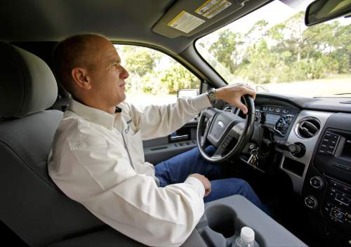In this Wednesday, Sept. 30, 2015, photo, Deseret Ranch general manager Erik Jacobsen drives around the property located in Deseret Ranch, Fla. Over the coming six decades, housing developments will replace citrus trees, and office parks will replace cattle-grazing under a plan being developed by the Mormon church-owned ranch located southeast of Orlando. (AP Photo/John Raoux)