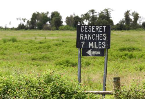 In this Wednesday, Sept. 30, 2015, photo, a sign gives directions to the Deseret Ranch offices in Deseret Ranch, Fla. Over the next six decades, the plan being developed by the Mormon church-owned Deseret Ranch promises to convert the largest undeveloped section of metro Orlando into more than a dozen bustling neighborhoods. (AP Photo/John Raoux)