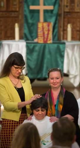 Steve Griffin  |  The Salt Lake Tribune  Kate Kelly and Tara Romney Barber lay their hands on Clare Julian Carbone at the First United Methodist Church in Salt Lake City during her ordination to the priesthood by a group called Association of Roman Catholic Women Priests  Sunday, October 18, 2015.  The Catholic Church does not recognize such ordinations, but the women priest movement  has ordained 220 women since beginning in Germany in 2002.