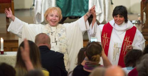 Steve Griffin  |  The Salt Lake Tribune  Bridget Mary Meehan, a bishop with the Association of Roman Catholic Women Priests, left, holds up the arms of Clare Julian Carbone at the First United Methodist Church in Salt Lake City on Sunday, October 18, 2015. Carbone's ordination was a first for Utah. The Catholic Church does not recognize such ordinations, but the women priest movement  has ordained 220 women since beginning in Germany in 2002.