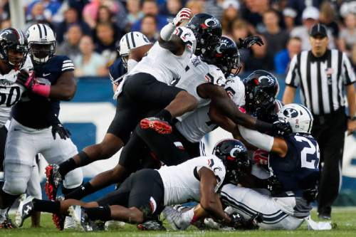 The Cincinnati defense takes down BYU running back Algernon Brown (24) after a carry in the first half of an NCAA college football game Friday, Oct. 16, 2015, in Provo, Utah. (Spenser Heaps/The Daily Herald via AP) MANDATORY CREDIT