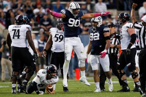 BYU defensive lineman Bronson Kaufusi (90) celebrates after drawing a fumble from Cincinnati quarterback Hayden Moore (8) which was quickly recovered by Moore in the first half of an NCAA college football game Friday, Oct. 16, 2015, in Provo, Utah. (Spenser Heaps/The Daily Herald via AP) MANDATORY CREDIT